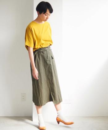 ワークなイメージのカーキのミモレスカートを女性らしく穿きこなしたい時は、ソックスとヒールを合わせて上品さをプラス。Tシャツもタックインですっきりと。ミモレ丈でバランスが取りにくい時はヒールで縦のラインを出してあげると、バランスよく着こなせます。