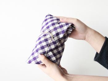 小さな布を使ったラッピング。包み込んだ後に麻紐を掛けて、ナチュラルで気さくなプレゼントに。