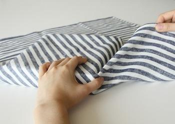 両端を折る時は、親指で中央を抑えて箱にしっかり添わせます。引っ張りながら、1の布の上に被せて。