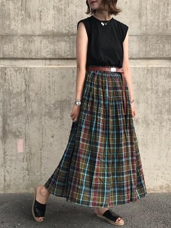 アースカラーをベースにしたマドラスチェックのマキシ丈スカートに、黒のノースリーブをボトムスイン&ベルトウエストマークですっきりときこなしたスタイリングです。ふんわりと軽やかなシルエットだから、シックな色合いも涼やかな印象に。