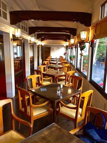 窓と照明に挟まれたカフェ「オーキッド」は、まるで豪華列車のようなインテリアが素敵ですね。
