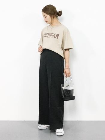 ベージュのロゴTシャツは黒のワイドパンツでちょっぴりシックに。足元をスニーカーにすることで、キメすぎない抜け感が演出できます。