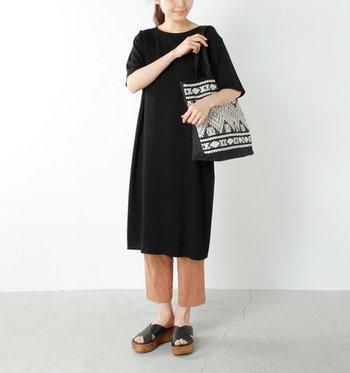 黒のエスニック柄トートバッグを、同じく黒のワンピースとブラウンパンツとのコーデに合わせたスタイリング。黒で色を合わせている分、エスニック柄が浮かずにパンツのブラウンが良い差し色になっています。