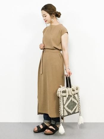 太めの紐を編み込んで作られたバッグに、タッセルやフリンジを盛り込んだ、エスニックテイストの強い巾着バッグ。ベージュのワンピースにデニムパンツを合わせ、きちんと感のあるワンピースをおしゃれにカジュアルダウン。ベーシックな着こなしだからこそ、デザイン性の強いバッグはアクセントになりますね。