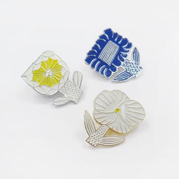 陶芸作家である鹿児島睦さんの図案を基にして作られたお花のブローチは、ちょっぴりレトロ感のあるデザインが魅力的なアイテム。甘すぎないフラワーブローチは用途を限定しないため、どこに付けてもしっくり馴染んでくれますよ。