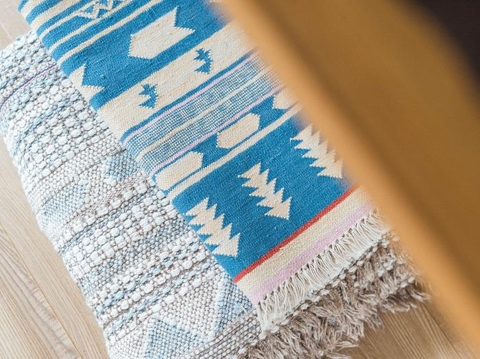 (奥)作家時代に齋藤さんが藍染めして手織りしたラグ。(手前)インドのジャイプールで職人によって織られたコットン100%のラグは、ブランド第一号のアイテム