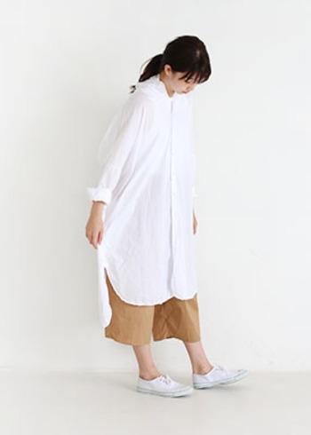 ホワイトのシャツワンピースに、ベージュのワイドパンツを合わせた着こなし。ちょっぴり短い丈のパンツを合わせて足首を出し、シャツの袖を折り返して手首を見せることで、シャツワンピースにありがちな詰まり感や気太り感を解消することができます。