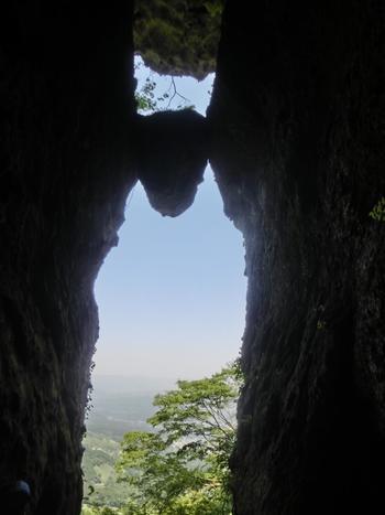 """外輪山の中程にある""""免の石""""。昔々、阿蘇の噴火によって飛び散った岩のひとつが、偶然にもこの間に挟まったのだと言われています。なんともミステリアスなパワースポットです。"""