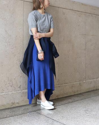 鮮やかなブルーのスカートはあえてグレーで大人っぽく。黒や白のTシャツよりも落ち着いた雰囲気になり、コーディネートにぬけ感が生まれます。