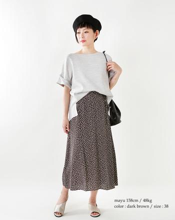 トレンドのドットスカートで、女性らしくシックにまとめて。足元はメタリックのサンダルでワンポイントに。