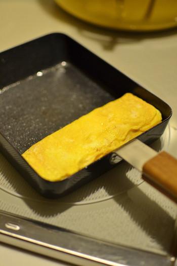 卵を奥に寄せたら、あいているところにサラダ油を塗ります。卵液を流し込んだら、奥にある卵を菜箸で持ち上げて卵の下の部分にも行き渡るようにします。
