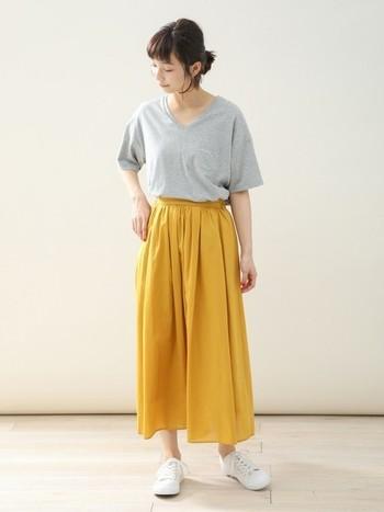 リラックス感のあるイエローのスカートにはフェミニンなVネックを合わせてキレイめにアップデート。ヘアスタイルをすっきりとまとめることで全身のバランスが整います。