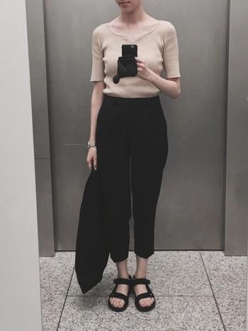 黒パンツにベージュカラーのトップスを合わせると上品で大人ぽい印象に。半端丈の黒パンツに同色のスポーツサンダルを合わせ、程よくカジュアルダウンさせています。