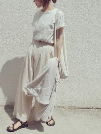 白Tシャツ×白リネンパンツのオールホワイトで軽やかにまとめたセットアップコーデのようなパンツルック。単調にならないよう、足元に黒のサンダルを合わせて程よく引き締めて。