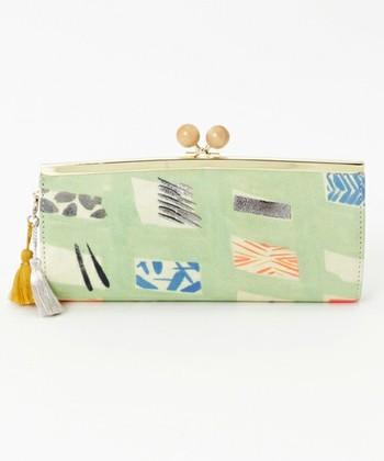 淡いカラーと大き目の金具が個性的なこちらの長財布。2色の小さなタッセルと、きめ細やかなレザーに描かれたイラストが印象的です。