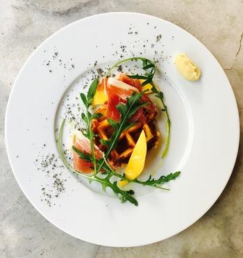 『熟成じゃがいもの塩ワッフル 生ハムとマンゴーと蜂蜜』。甘さと酸味、彩りも美しく、斬新な料理にきっと驚くはずです。