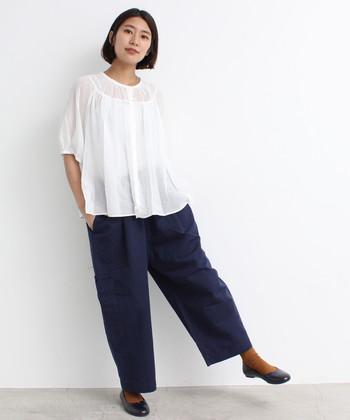 夏らしい透け感が涼しげな印象の白ブラウスに、ネイビーのワイドパンツを合わせた着こなしです。温度や気分に合わせて、足元をサンダルにしたり、素足×パンプスのスタイリングもおすすめ。