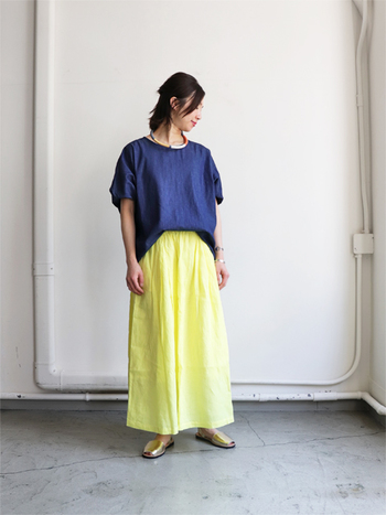 鮮やかなイエローのロングスカートに、ネイビーのデニムプルオーバーを合わせた着こなしです。薄めのイエローと濃いネイビーの組み合わせが、爽やかな印象を与えてくれます。水色系のトップスと合わせても◎