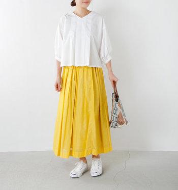パッと目を惹くイエローのスカートは、ギャザーがあしらわれたデザインが特徴。白トップスとスニーカーでとことん爽やかにまとめつつ、個性的なデザインのバッグをアクセントにプラスしています。