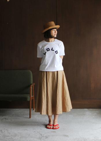 シンプルなロゴTシャツにベージュのスカートは、ナチュラルさんの定番スタイル。そこへ赤いサンダルをプラスして、キュートなアクセントに。
