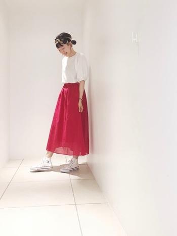 ふわっとしたシルエットと、素材のさりげない透け感が柔らかな印象のマキシスカート。白トップスとスニーカーを合わせて、レディな印象の赤スカートを上手にカジュアルダウンしています。