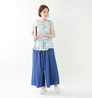 ブルーのリバティプリントノースリーブは、フロントにあしらわれたプリーツやAラインの女性らしいシルエットがポイントの一枚。ネイビーのワイドパンツと合わせて、爽やかなブルートーンの着こなしに。