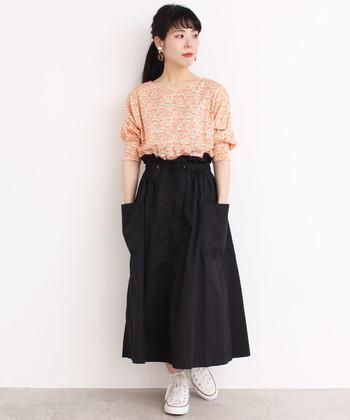 オレンジが印象的なリバティプリントトップスに、黒のロングスカートを合わせたスタイリング。ウエストにデザインのあるスカートをタックインして着こなせば、トレンド感もアップします。白のスニーカーで、黒スカートが重くならないような組み合わせに。