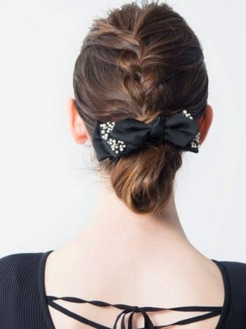 真ん中に編み込みを入れて縦のラインを強調した可愛らしいまとめ髪です。シックな髪飾りを低めの位置に持ってくることで、よりフォーマルな印象になっています。