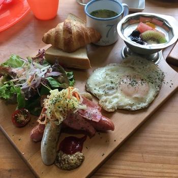大きな木のプレートに、ソーセージ、サラダ、パン、卵などが盛りだくさんのモーニングセット。素朴ながら食べごたえがあって、朝から元気になれそう。