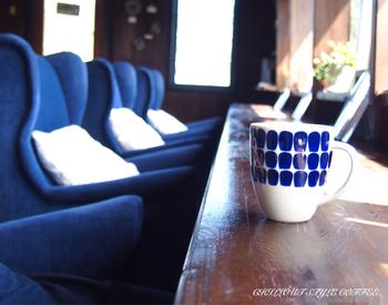 大きな窓に向かって青いソファーが並んでいます。ボリュームを絞ったBGMが心地よく、いつまでもくつろいでいたくなる雰囲気です。そして、アラビアのカップに注がれたコーヒーも。コーヒー豆の種類も豊富なので、迷ったらスタッフの方に相談してみましょう。