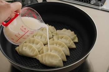 いくつかの方法がありますが、基本的には餃子を火にかけてしばらくしたら、小麦粉(片栗粉)を溶いた水を加えます。そのあとは、普通の餃子を焼くのと手順はほとんどかわりません。