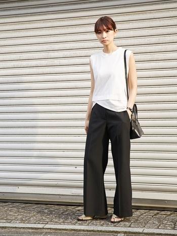 白のノースリーブトップス×黒のワイドパンツを合わせたモノトーンスタイルは、足元にフラットサンダルを合わせて軽やかに。さらにヘアスタイルをコンパクトにまとめることで、大人クールな印象を作ります。