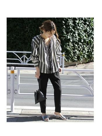 黒パンツにモノトーンのストライプシャツと合わせたコーディネート。ゆったりとしたシルエットに大人の余裕が感じられます。さらにシルバーのシューズで、足元をクールなスパイスを加えて。