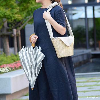 夏のお出かけにぜひひとつ欲しいかごバッグ。こちらは、カジュアルなかごバッグにリネンを合わせることで上品な大人感を印象づけています。持ち手のリネンの長さを調節して、ショルダーにも手提げにもできる2WAY仕様もうれしい。
