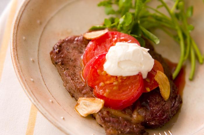 薄めのステーキでも、焼きトマトとサワークリームをアレンジするとこんなに豪華な雰囲気に!真っ白なサワークリームで華やかさが演出できますね。