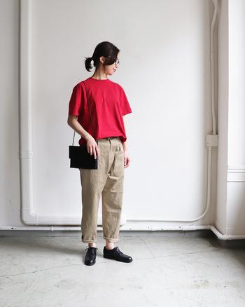 存在感抜群の赤の無地Tシャツは、ベージュのチノパンと合わせてシンプルにまとめて。小物は黒で合わせれば、Tシャツが主役のおしゃれなスタイリングに。