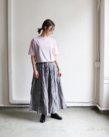 薄いピンクの無地Tシャツに、シワ感がおしゃれなグレーのロングスカートを合わせたコーディネート。ピンクは子どもっぽくなりすぎると感じる方は、グレーや黒などのダークトーンカラーのボトムスを合わせると馴染みやすいです。