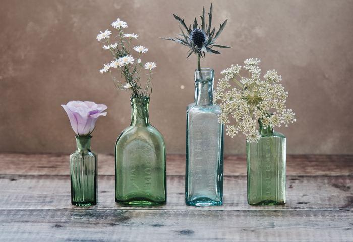 それぞれ色味や形の異なる花を、デザインの違うボトルにIN。高さのあるものを真ん中に配置し、低いものを外側に配置することでアーチのようなシルエットになるよう意識。そうすることで安定感も生まれ、華やかだけど賑やかになりすぎない統一感のあるコーディネートになります。