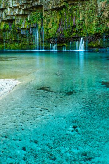 人気の秘密は、滝壺にあり!透き通ったエメラルドグリーンの滝壺がSNSでも話題になり、多くの観光客が訪れるスポットになりました。透き通った美しい色合いに心奪われますね。
