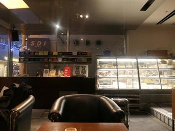 """店内は吹抜けを生かした四層構造。 無造作に置かれたイベントや美術展などの案内カードが、お店を""""カフェ以上""""の空間に演出✩スイーツのショーウィンドウには『くまちゃんショコラ』『ゴルゴンゾーラのチーズケーキ』など、この店の人気作が揃って♪"""