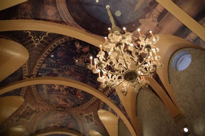 貴族の館を模した「ヴェネチアン・グラス美術館」、水を湛えた「季節の庭園」を中心として、「現代ガラス美術館」やミュージアムショップ、カフェや体験工房等などが、自然豊かな環境の中に配されています。  【画像は、15世紀から18世紀にかけて生み出された秀逸な作品群を展示する「ヴェネチアン・グラス美術館」内。豪奢なシャンデリアと天井画も見事。】