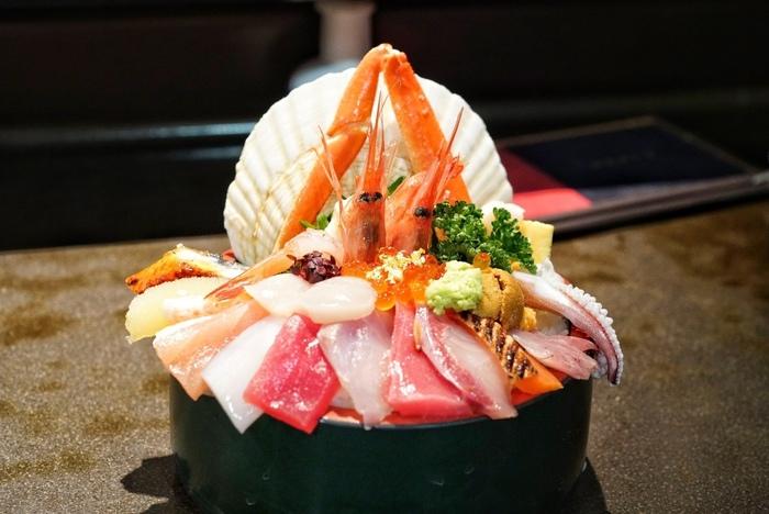 60年続く老舗寿司店「山さん寿司 本店」の海鮮丼 3,000円は写真映え間違いなしの豪快な盛り付け。帆立貝を背景に、カニやエビを立体的に盛り付け18種のネタを使った一品。「特上にぎり(10貫)3,000円」や雲丹いくら丼もおすすめです。