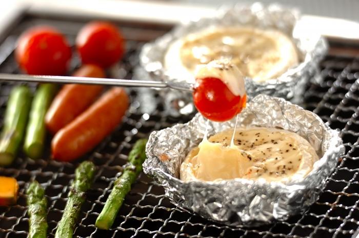 炭火の上でチーズフォンデュをするなら、カマンベールチーズがおすすめ。カマンベールの形をそのまま活かしアルミで囲ったら網の上に乗せるだけ。野菜も一緒に焼きつつ楽しみましょう。