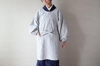 300年の伝統を持つ、亀田縞の生地で作られた割烹着。ふんわりとした仕立ては、手仕事ならではの仕上がりです。