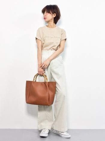 コンパクトなTシャツの袖をすこしロールアップして二の腕を長く見せています。ブラウン系のバッグをチョイスすることで、全体がぐっと引き締まっています。