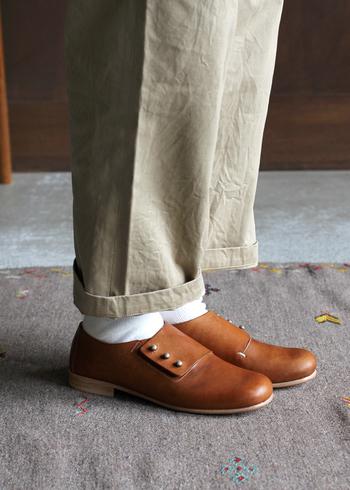 甲に並んだ3つのホックがアクセントになっている、オールハンドメイドのクラシックなレザーシューズです。甲の部分をすっぽりくるむ仕様のフォルムは見た目の上品さに加え、抜群の安定感。じっくりと丁寧に鞣された革が、履くほどに足の形に馴染んでくれます。