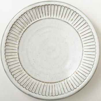 こちらの「しのぎ尺皿」は、熊本県にある小代焼(しょうだいやき)の窯元「小代瑞穂釜」の2代目、福田るいさんの作品です。小代の土と釉薬で作られた素朴で温かみのある風合いと、しのぎの立体的な模様が印象的。上品な雰囲気の白の大皿は、和洋どんな食卓シーンにも馴染むシンプルさも魅力です。