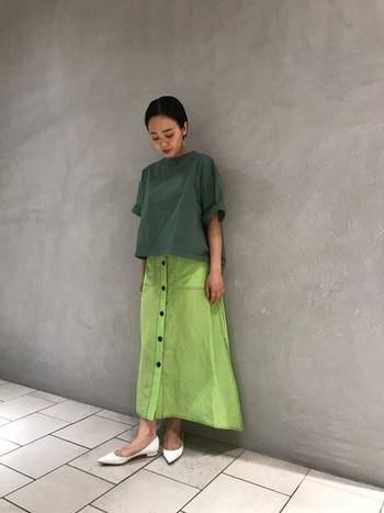 モスグリーンのTシャツに、同系色のロングスカートを合わせた技ありコーデ。足元はグリーンを邪魔しない白をセレクトしています。パンプスを合わせて女性らしく仕上げるテクニックも真似したい。
