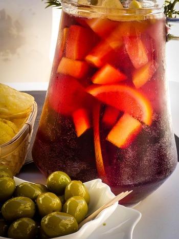 """サングリアは、ワインにフルーツやスパイスなどでフレーバーを足したもので、スペインやポルトガルで愛されているワインカクテルです。スペイン語で「sangre」は""""血""""を意味し、赤ワインで作ることが多かったことからその名が付いたともいわれます。"""