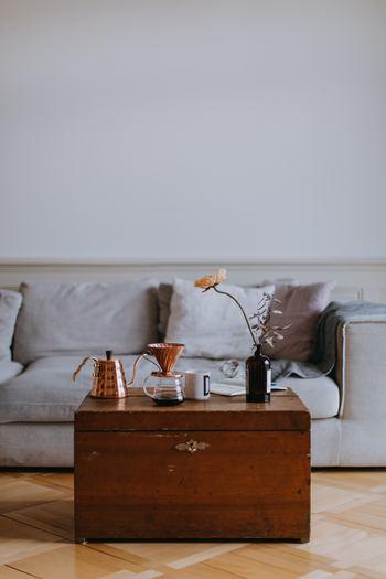 雰囲気のある飴色のアンティーク調テーブル。その上に、一輪のお花とグリーンを1本ずつ薬瓶に入れて飾っても素敵。お花は家具にも馴染む落ち着いたカラーのものを、少し高さを出して飾ることで、低めのインテリア空間に立体感が生まれ、お洒落なバランスに。